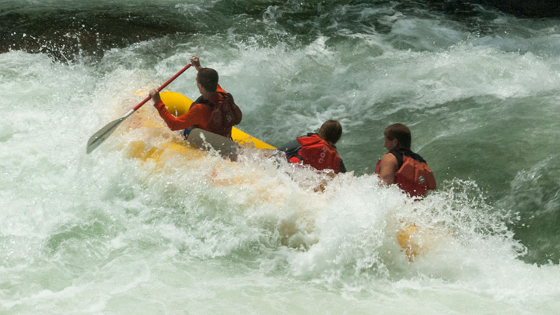 Raft goes over the falls sideways. People get wet